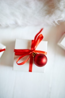 Boîte de cadeau de noël avec bonnet de noel, décorations rouges sur fond en bois blanc, noël, hiver, concept de nouvel an, mise à plat, vue du dessus, espace copie