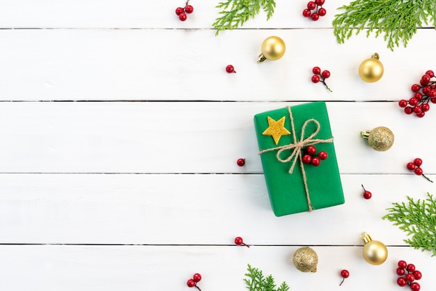 Boîte de cadeau de noël, branches d'épinette, fruits rouges sur fond en bois.
