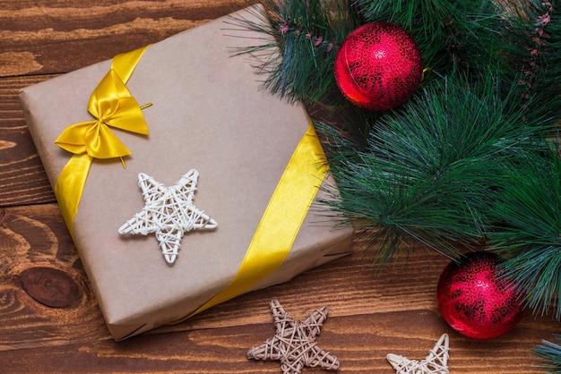 Boîte de cadeau de noël et décor de branche d'arbre sur table en bois. mise à plat, vue de dessus
