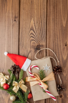 Boîte de cadeau de noël, décor de nourriture et branche de sapin sur une table en bois. vue de dessus avec fond
