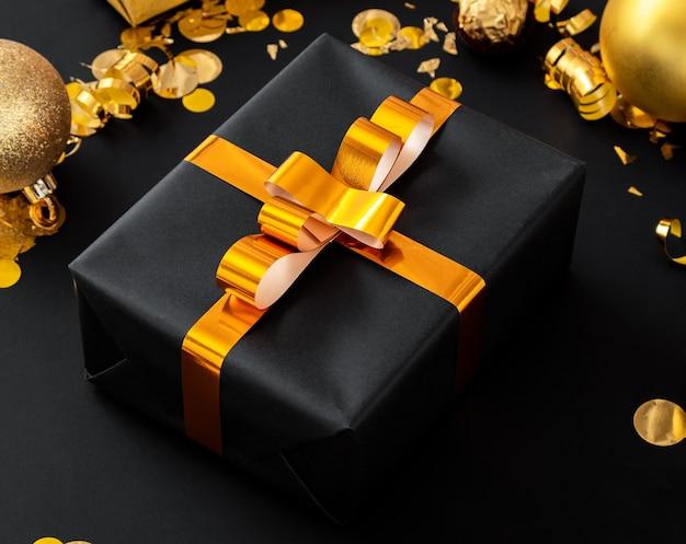 Boîte cadeau de noël noir avec noeud de ruban d'or et décor de fête de noël or sur fond noir.