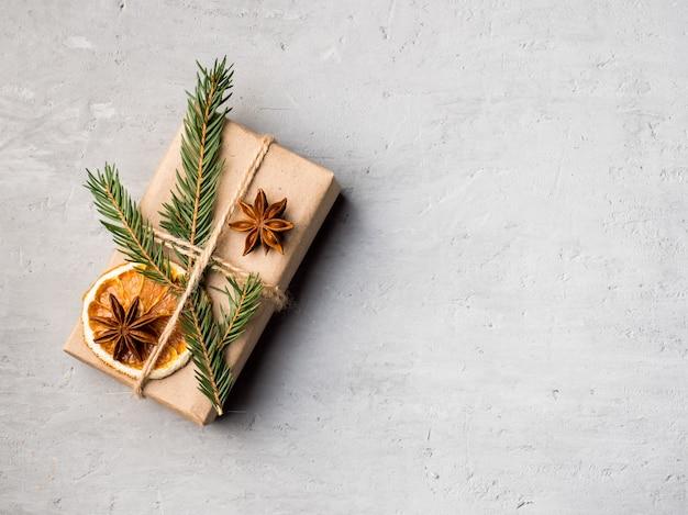 Boîte de cadeau de noël en papier avec des épices d'hiver sur un béton gris