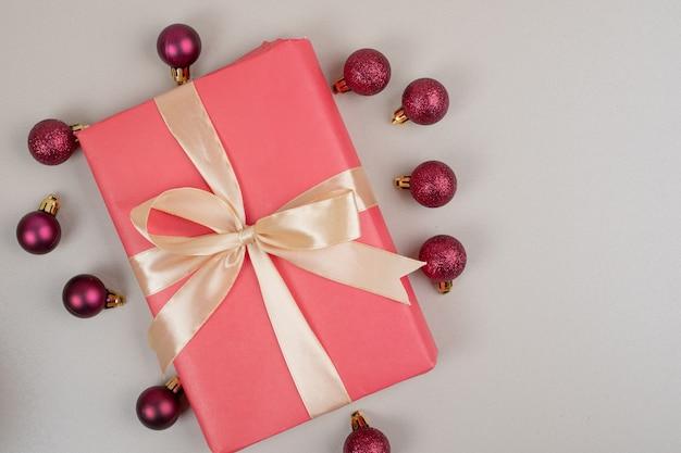 Boîte-cadeau de noël avec de petites boules rouges sur une surface blanche