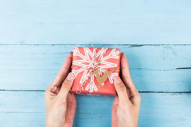 Boîte de cadeau de noël à portée de main, préparation pour les vacances. vue de dessus