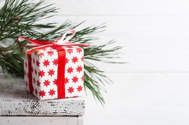 Boîte-cadeau de noël rouge et pin dans un intérieur scandinave blanc.