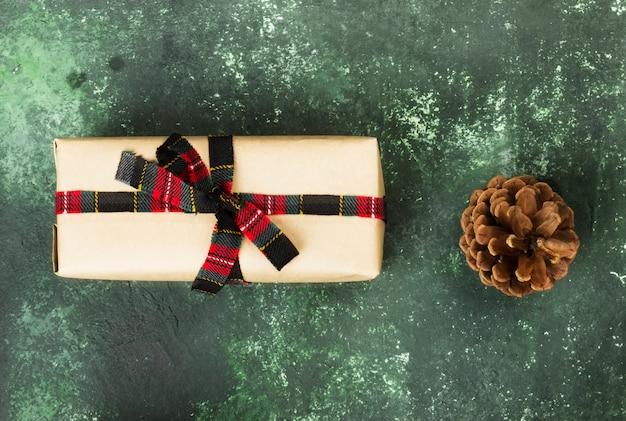 Boîte avec un cadeau de noël sur une surface verte