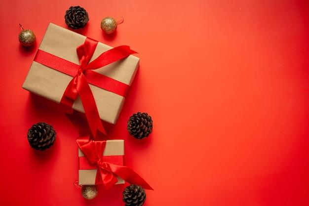 Boîte de cadeau avec noeud de ruban rouge sur fond rouge