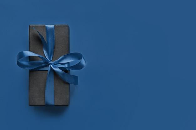 Boîte cadeau noire enveloppée de ruban bleu sur une surface bleue classique.