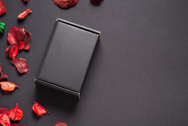 Boîte cadeau noire et fleurs séchées sur fond noir, présent