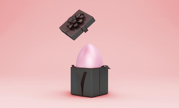 Boîte cadeau noire avec oeuf de pâques rose à l'intérieur sur mur rose