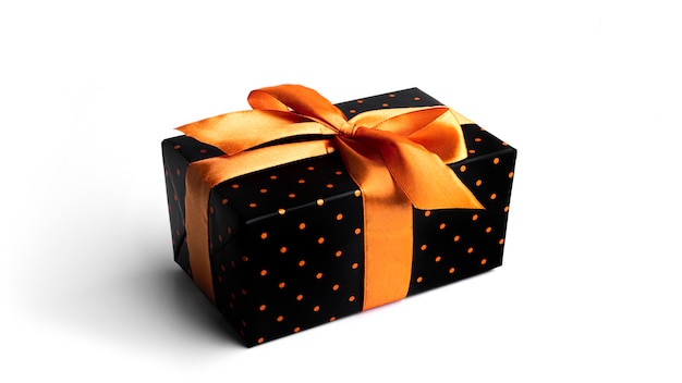 Boîte cadeau noire avec ruban d'or isolé sur surface blanche