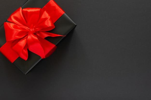 Boîte cadeau noire avec ruban rouge et arc sur mur noir, mise à plat, vue du dessus