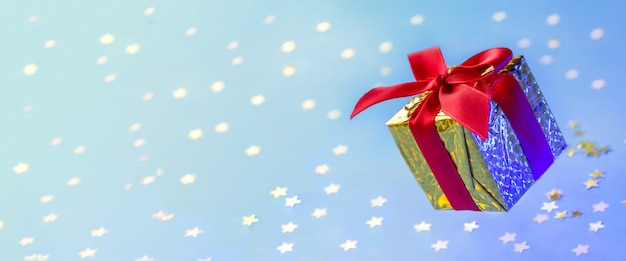 Boîte cadeau or bannière avec ruban rouge flottant sur fond bleu avec des étoiles brillantes