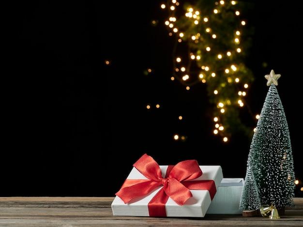Boîte-cadeau ouvert vide de noël sur table en bois contre les lumières floues, espace pour le texte