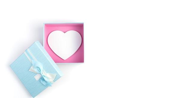 Boîte cadeau ouverte avec un cœur blanc à l'intérieur sur un fond blanc.