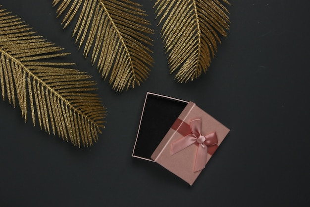 Boîte cadeau ouverte sur fond noir avec des feuilles de palmier dorées. mise à plat de la mode. vue de dessus