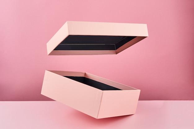 Boîte cadeau ouverte rose isolée sur fond rose. conteneur de cadeau vide. maquette vierge avec boîte volante.