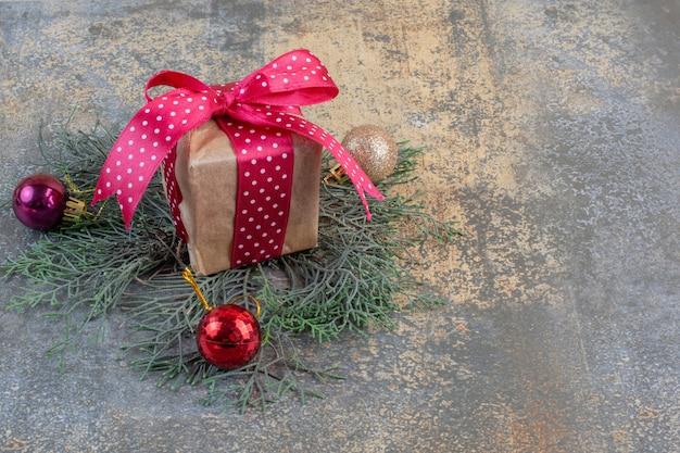 Une boîte cadeau en papier avec un arc et une boule de noël. photo de haute qualité