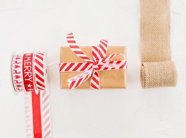 Boîte cadeau en papier kraft avec ruban près du rouleau élastique