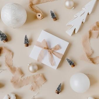 Boîte cadeau en papier avec noeud papillon et jouets de noël: sapins, boules, rubans sur surface beige pastel