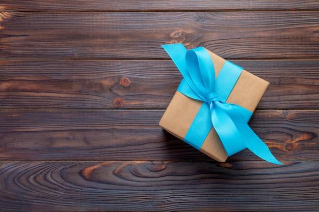 Boîte-cadeau en papier avec ruban bleu sur fond de bois foncé. vue de dessus avec espace de copie