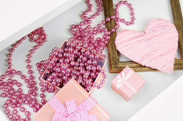 Boîte-cadeau et perles dans le tiroir de bureau ouvert se bouchent