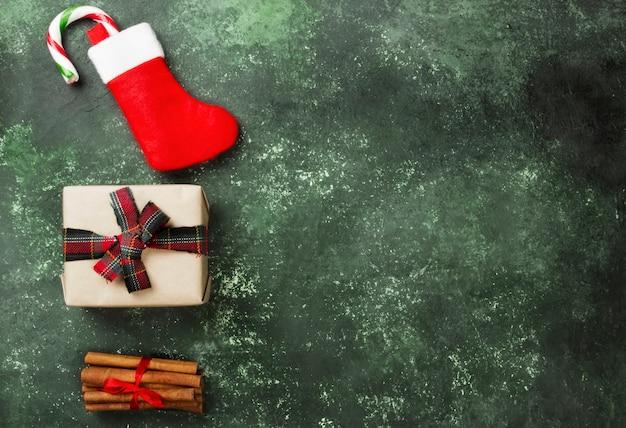 Boîte avec cadeau pour noël et bas avec une canne en bonbon sur une surface verte.