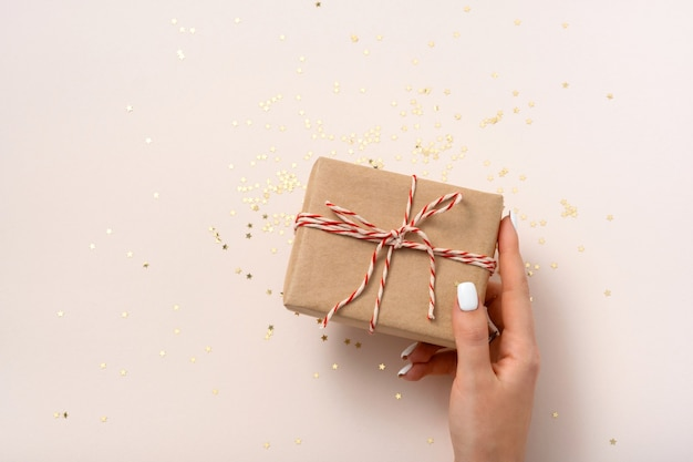 Boîte-cadeau de prise de main féminine en papier kraft avec ruban du nouvel an blanc-rouge et confettistars d'or sur un espace de copie de fond beige, mise à plat. noël, mariage