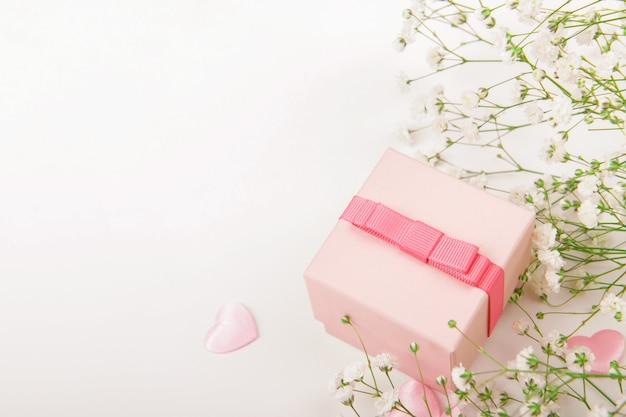 Boîte cadeau rose sur fond rose avec de petites fleurs blanches, célébration de la saint-valentin