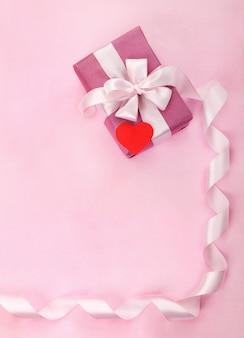 Boîte cadeau rose, noeud blanc, long ruban incurvé, coeur rouge en papier et espace vide pour le texte.