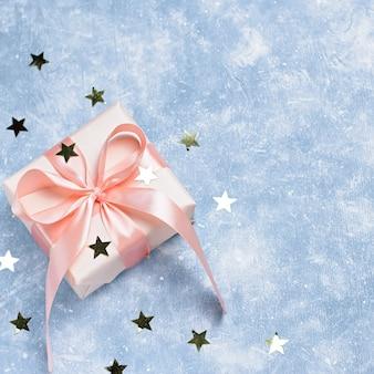Boîte cadeau rose avec noeud et confettis dorés sur bleu