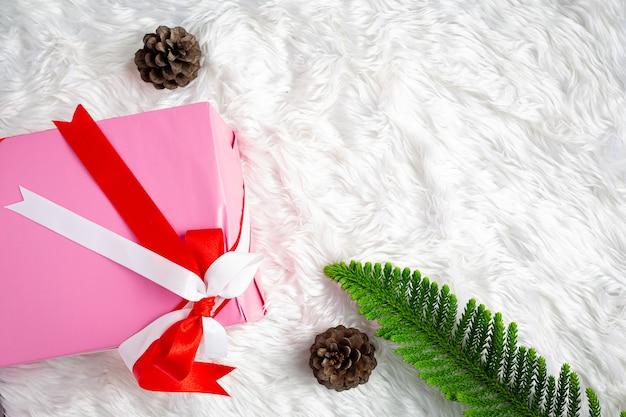 Une boîte cadeau rose avec ruban sur tissu de fourrure blanc