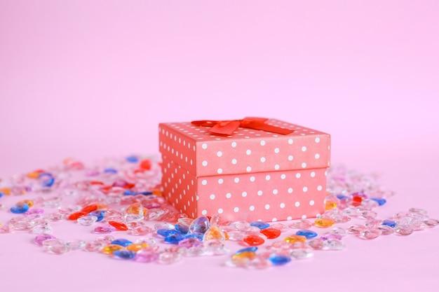Boîte cadeau rouge avec des billes sur fond rose