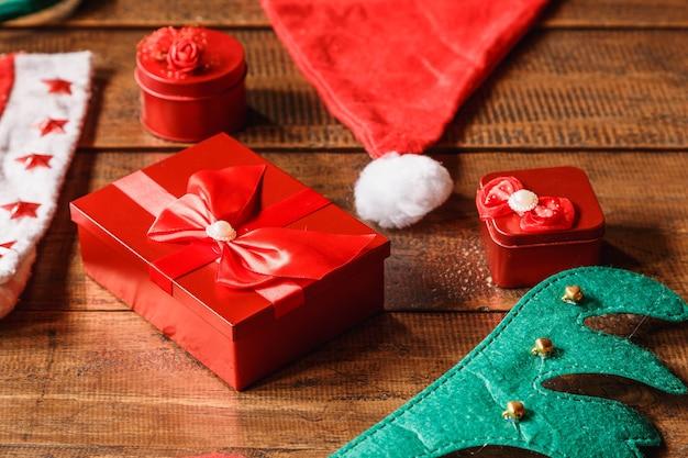 Boîte-cadeau rouge et bonnet de noel sur table en bois