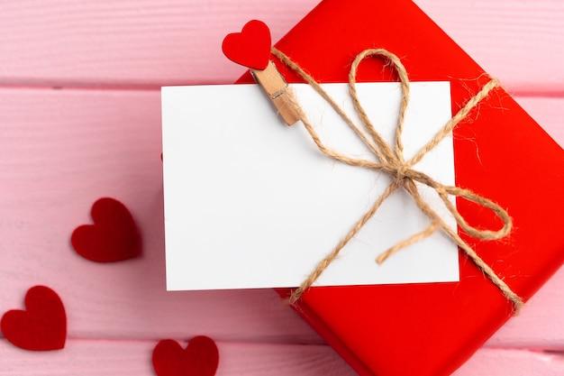 Boîte-cadeau rouge et carte de voeux sur surface rose