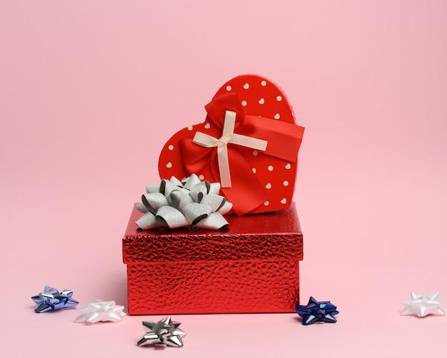 Boîte cadeau rouge sur fond rose, fond festif, gros plan