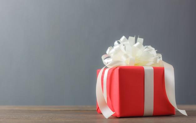 Boîte cadeau rouge et noeud blanc avec ribbon.accessories bonne année ou joyeux anniversaire concept.object ou joyeux noël sur le bois rustique brun moderne au studio de bureau à domicile.