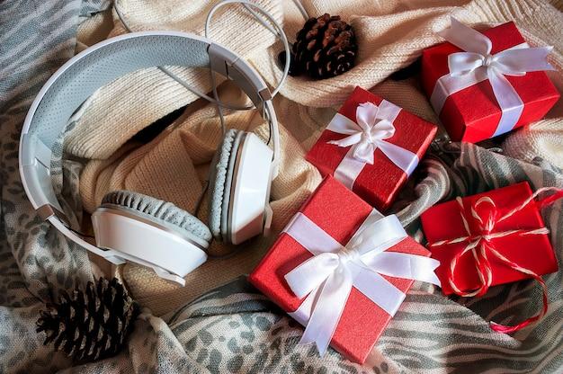 Boîte-cadeau avec ruban blanc, casque et écharpe sur un chandail blanc. sur la lumière