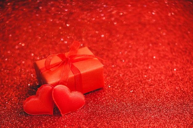 Boîte cadeau saint valentin et deux coeurs sur des étincelles rouges avec espace de copie.