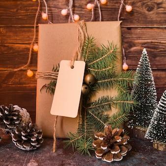 Boîte cadeau sapin décoré brindille avec étiquette près d'accrocs