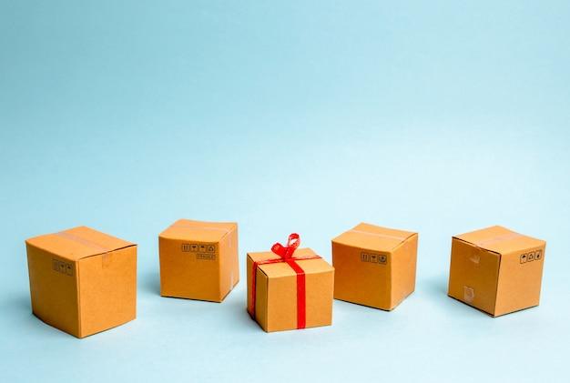 Une boîte cadeau se trouve parmi d'autres boîtes. le concept de vente de biens et services, achat de cadeaux