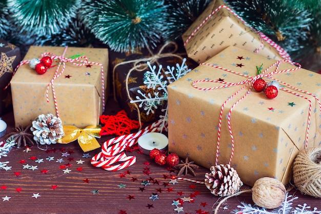 Boîte de cadeau de vacances de noël sur la table de fête décorée avec des branches de sapin de cônes de pin