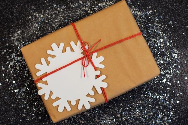 Boîte de cadeaux de noël présente en papier kraft et flocon de neige blanc. thème des vacances d'hiver. mise à plat.