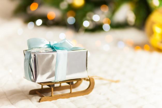 Boîte de cadeaux en papier pailleté sur le traîneau de noël. concept minimal du nouvel an.