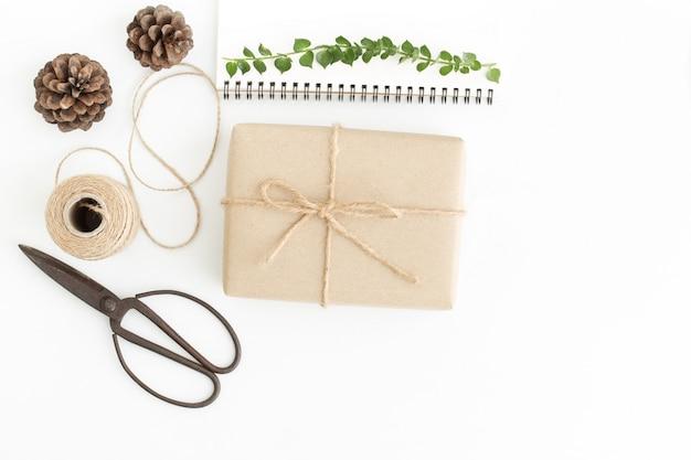 Boîte à cadeaux vue de dessus et accessoires sur blanc, papier cadeau fait main sur sol blanc