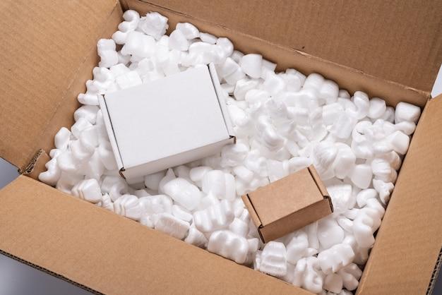 Boîte en carton sur des arachides d'emballage d'expédition de remplissage blanc en vrac