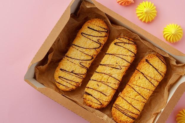 Boîte en carton avec des biscuits à l'avoine sur table rose