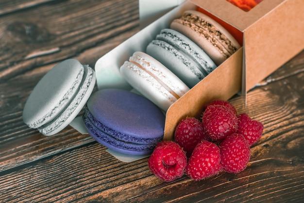 Boîte en carton avec biscuits macarons et framboises