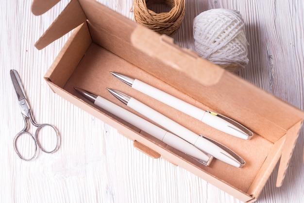 Boîte en carton brun, étui avec stylos à l'intérieur sur un bureau en bois