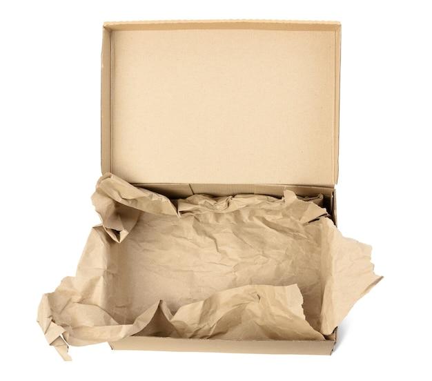 Boîte en carton brun rectangulaire vide ouvert pour le transport et l'emballage de marchandises isolées sur fond blanc, vue de dessus. en bas se trouve un morceau de papier brun